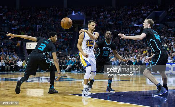 Stephen Curry of the Golden State Warriors makes a no look pass as he is defended by Jeremy Lamb kemba Walker and Cody Zeller of the Charlotte...