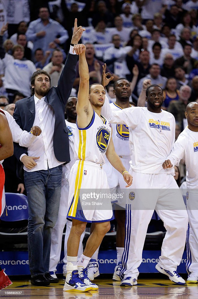 Stephen Curry #30 of the Golden State Warriors makes a three-point basket in front of his bench during their game against the Los Angeles Clippers at Oracle Arena on January 2, 2013 in Oakland, California.