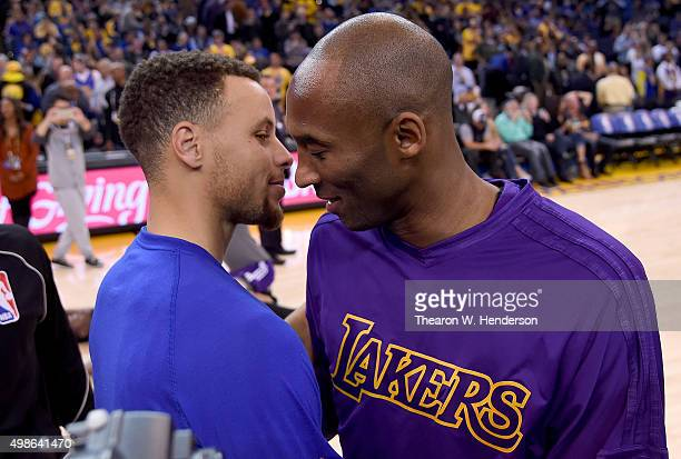 Stephen Curry of the Golden State Warriors meets at center court with Kobe Bryant of the Los Angeles Laker prior to the start of their NBA basketball...