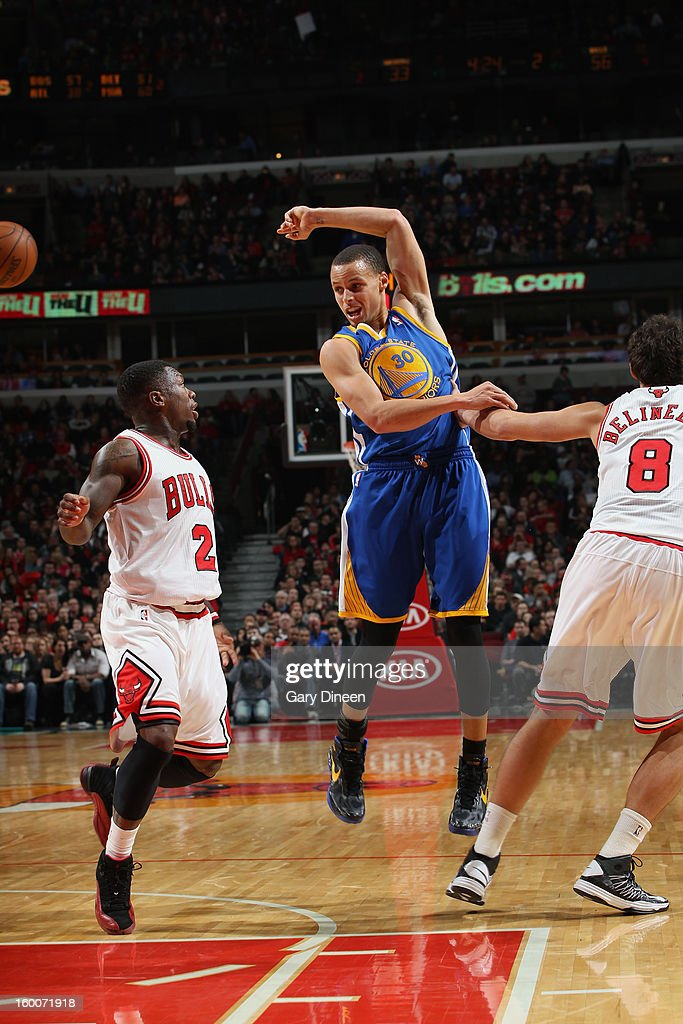 Stephen Curry #30 of the Golden State Warriors passes against (L-R) Nate Robinson #2 and Marco Belinelli #8 of the Chicago Bulls on January 25, 2012 at the United Center in Chicago, Illinois.