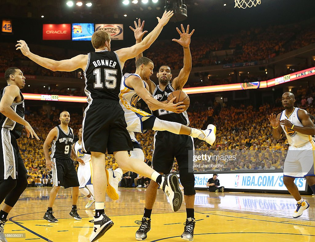 Stephen Curry #30 of the Golden State Warriors passes against Tim Duncan #21 and Matt Bonner #15 of the San Antonio Spurs in Game Three of the Western Conference Semifinals during the 2013 NBA Playoffs on May 10, 2013 at the Oracle Arena in Oakland, California.