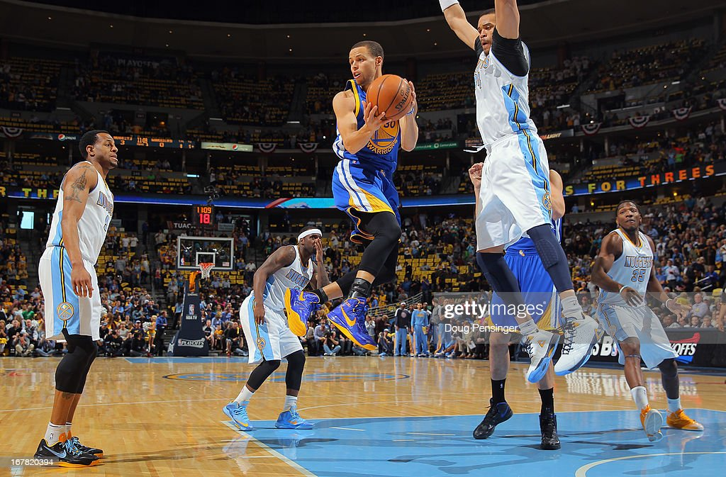 Stephen Curry #30 of the Golden State Warriors passes the ball against the defense of JaVale McGee #34 of the Denver Nuggets during Game Five of the Western Conference Quarterfinals of the 2013 NBA Playoffs at the Pepsi Center on April 30, 2013 in Denver, Colorado.