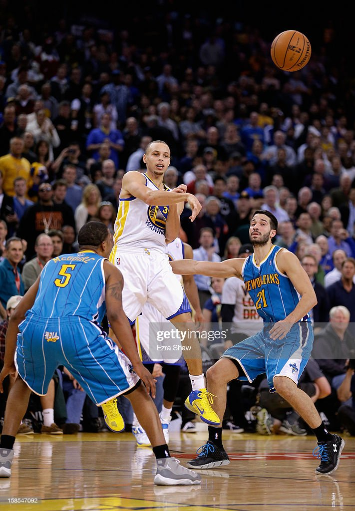 Stephen Curry #30 of the Golden State Warriors passes the ball between Dominic McGuire #5 and Greivis Vasquez #21 of the New Orleans Hornets at Oracle Arena on December 18, 2012 in Oakland, California.