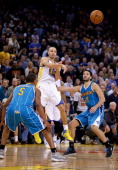 Stephen Curry of the Golden State Warriors passes the ball between Dominic McGuire and Greivis Vasquez of the New Orleans Hornets at Oracle Arena on...