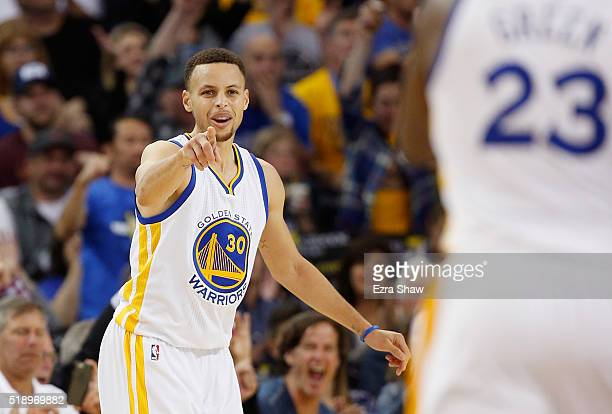 Stephen Curry of the Golden State Warriors points back to Draymond Green of the Golden State Warriors after Green passed him the ball for a...