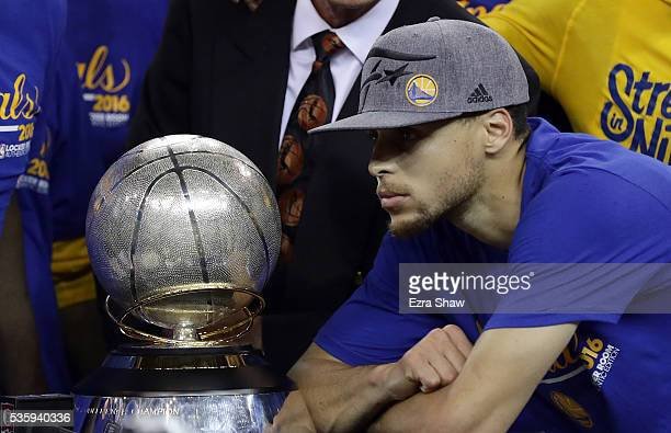 Stephen Curry of the Golden State Warriors poses with the Western Conference Trophy they beat the Oklahoma City Thunder in Game Seven of the Western...