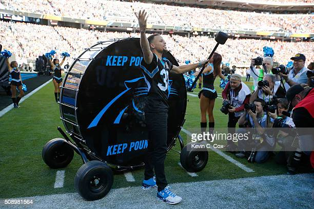 Stephen Curry of the Golden State Warriors prepares to hit the 'Keep Pounding' drum for the Carolina Panthers prior to Super Bowl 50 against the...