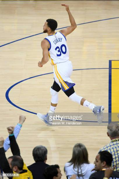 Stephen Curry of the Golden State Warriors reacts after a threepoint basket against the San Antonio Spurs during Game One of the NBA Western...