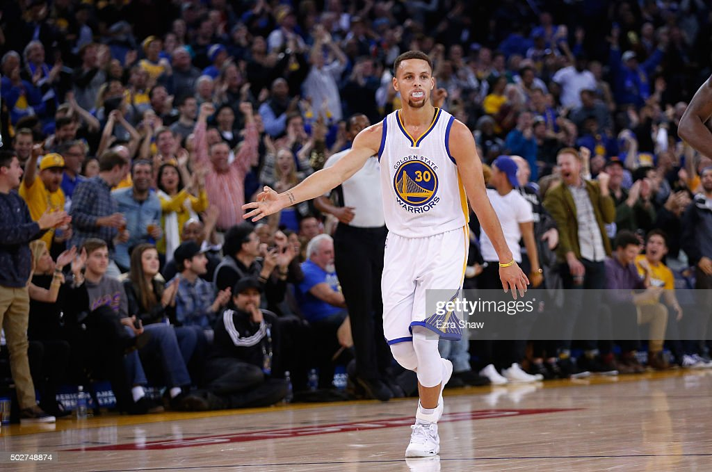 Stephen Curry of the Golden State Warriors reacts after he made a threepoint basket against the Sacramento Kings at ORACLE Arena on December 28 2015...
