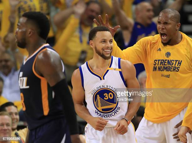 Stephen Curry of the Golden State Warriors reacts after hitting a threepoint basket against the Utah Jazz with David West during Game Two of the NBA...