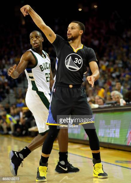 Stephen Curry of the Golden State Warriors reacts after making a threepointer as Khris Middleton of the Milwaukee Bucks defends during the game at...