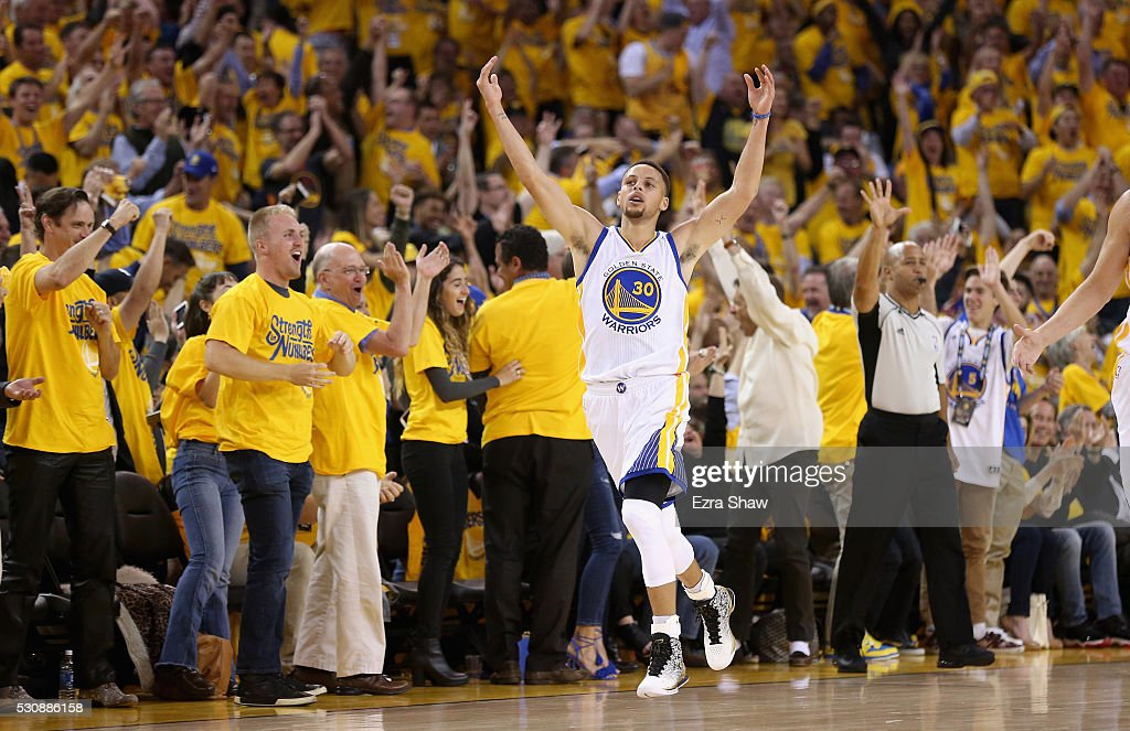 Stephen Curry of the Golden State Warriors reacts after making a threepoint basket in the first quarter against the Portland Trail Blazers during...