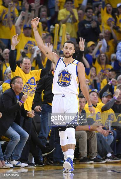 Stephen Curry of the Golden State Warriors reacts after making a threepoint shot over Maurice Harkless of the Portland Trail Blazers in the third...