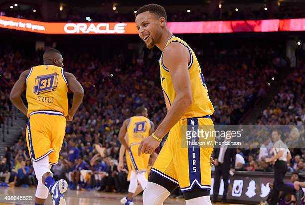 Stephen Curry of the Golden State Warriors reacts after scoring against the Los Angeles Lakers during an NBA basketball game at ORACLE Arena on...