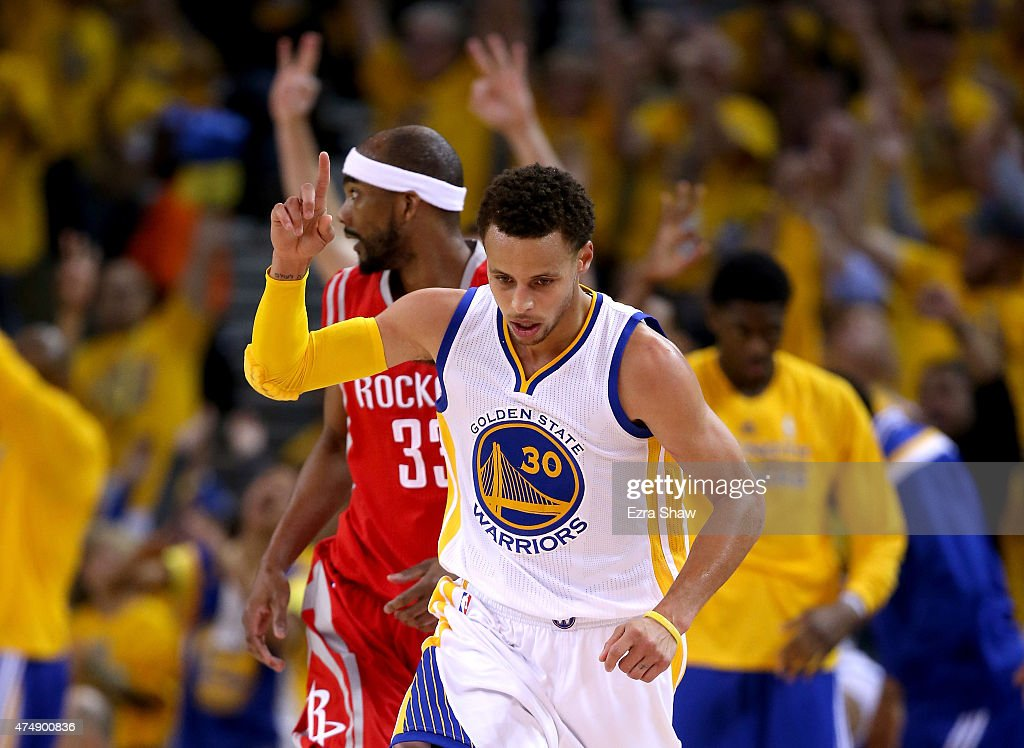 <a gi-track='captionPersonalityLinkClicked' href=/galleries/search?phrase=Stephen+Curry+-+Basketball+Player&family=editorial&specificpeople=5040623 ng-click='$event.stopPropagation()'>Stephen Curry</a> #30 of the Golden State Warriors reacts in front of <a gi-track='captionPersonalityLinkClicked' href=/galleries/search?phrase=Corey+Brewer&family=editorial&specificpeople=234749 ng-click='$event.stopPropagation()'>Corey Brewer</a> #33 of the Houston Rockets after making a three-pointer in the first half during game five of the Western Conference Finals of the 2015 NBA Playoffs at ORACLE Arena on May 27, 2015 in Oakland, California.