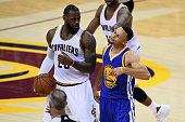 Stephen Curry of the Golden State Warriors reacts to a foul call during the fourth quarter as LeBron James of the Cleveland Cavaliers looks on in...