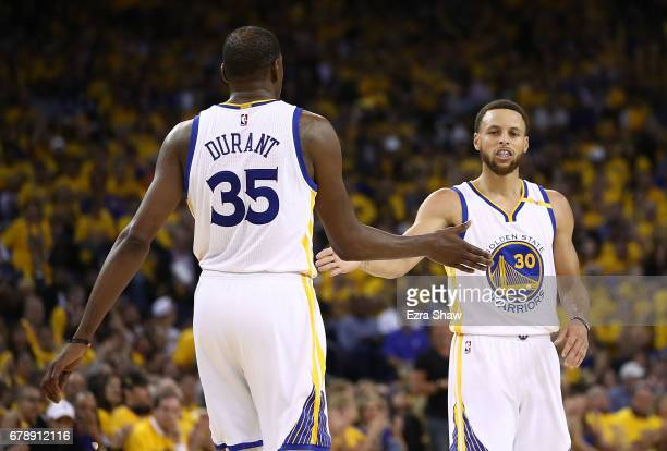 Stephen Curry of the Golden State Warriors reacts with Kevin Durant against the Utah Jazz during Game Two of the NBA Western Conference SemiFinals at...