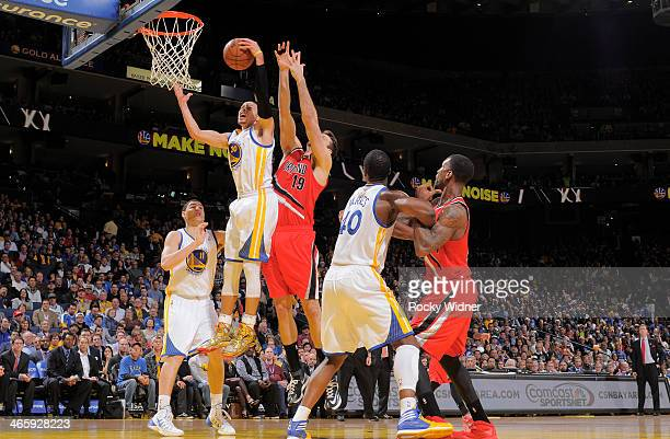 Stephen Curry of the Golden State Warriors rebounds against Joel Freeland of the Portland Trail Blazers on January 26 2014 at Oracle Arena in Oakland...