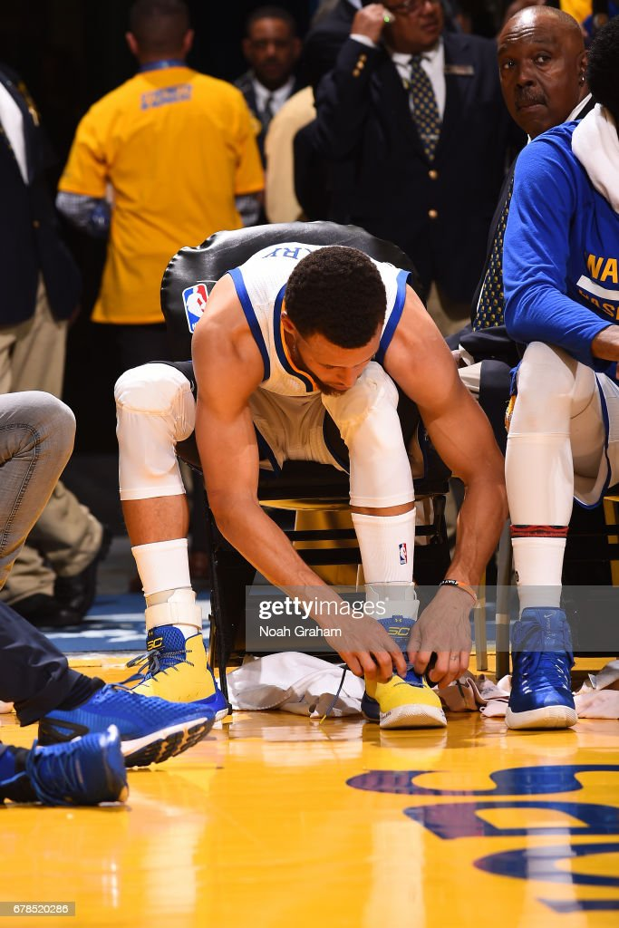 Stephen Curry #30 of the Golden State Warriors re-tapes his ankle and ties his shoes during Game One of the Western Conference Semifinals against the Utah Jazz during the 2017 NBA Playoffs on May 2, 2017 at ORACLE Arena in Oakland, California.