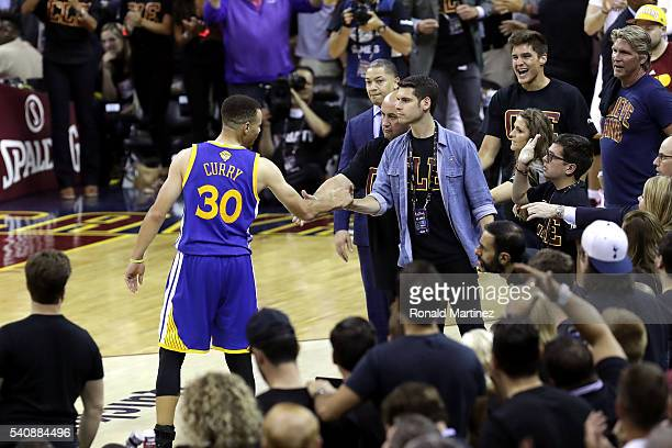 Stephen Curry of the Golden State Warriors shakes hands with Andrew Forbes son of Cavaliers minority owner Nate Forbes after throwing his mouthguard...