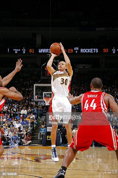 Stephen Curry of the Golden State Warriors shoots a jump shot against Chuck Hayes of the Houston Rockets during the game at Oracle Arena on October...