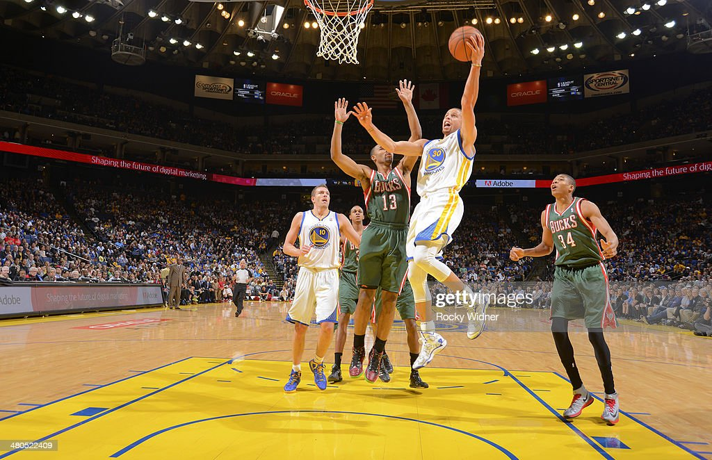 Stephen Curry #30 of the Golden State Warriors shoots a layup against <a gi-track='captionPersonalityLinkClicked' href=/galleries/search?phrase=Ramon+Sessions&family=editorial&specificpeople=805440 ng-click='$event.stopPropagation()'>Ramon Sessions</a> #13 of the Milwaukee Bucks on March 20, 2014 at Oracle Arena in Oakland, California.