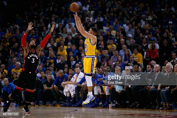 Stephen Curry of the Golden State Warriors shoots a threepoint basket over James Johnson of the Toronto Raptors at ORACLE Arena on November 17 2015...