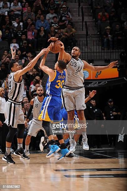 Stephen Curry of the Golden State Warriors shoots against Danny Green of the San Antonio Spurs and Boris Diaw of the San Antonio Spurs on March 19...