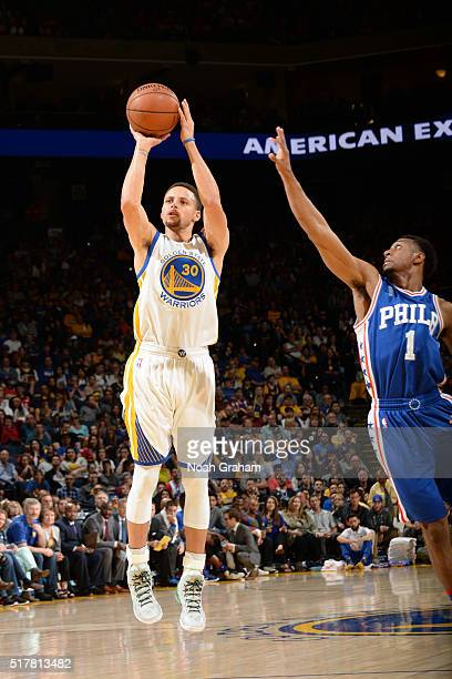 Stephen Curry of the Golden State Warriors shoots against Ish Smith of the Philadelphia 76ers on March 27 2016 at Oracle Arena in Oakland California...