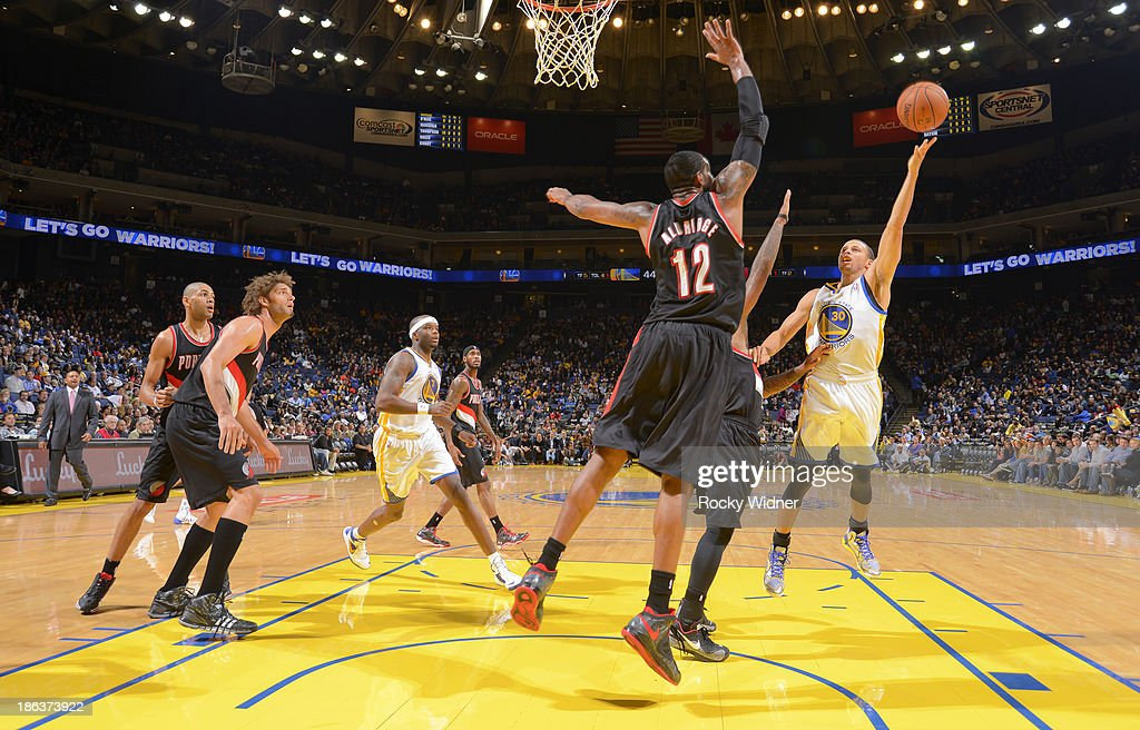Stephen Curry #30 of the Golden State Warriors shoots against <a gi-track='captionPersonalityLinkClicked' href=/galleries/search?phrase=LaMarcus+Aldridge&family=editorial&specificpeople=453277 ng-click='$event.stopPropagation()'>LaMarcus Aldridge</a> #12 of the Portland Trail Blazers on October 24, 2013 at Oracle Arena in Oakland, California.