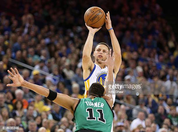 Stephen Curry of the Golden State Warriors shoots over Evan Turner of the Boston Celtics at ORACLE Arena on April 1 2016 in Oakland California NOTE...