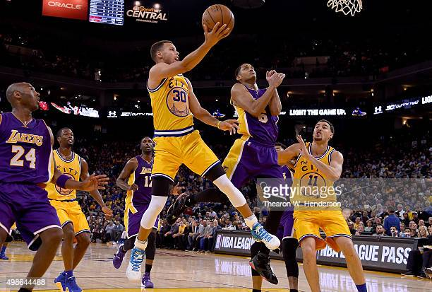 Stephen Curry of the Golden State Warriors shoots over Jordan Clarkson of the Los Angeles Lakers during their NBA basketball game at ORACLE Arena on...