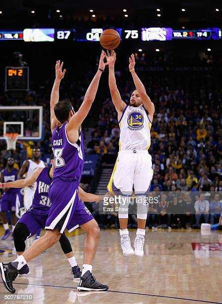 Stephen Curry of the Golden State Warriors shoots over Omri Casspi of the Sacramento Kings at ORACLE Arena on December 28 2015 in Oakland California...