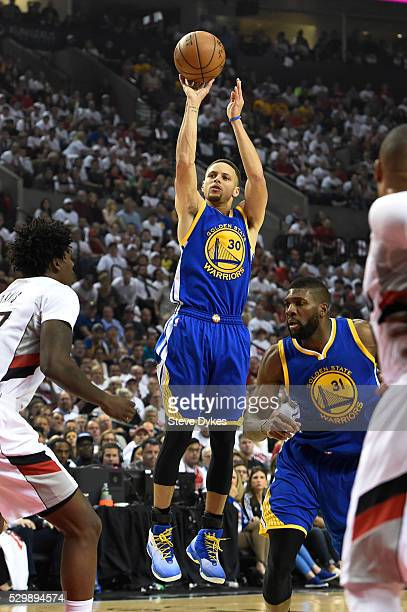Stephen Curry of the Golden State Warriors shoots the ball on Ed Davis of the Portland Trail Blazers during the first quarter of Game Four of the...