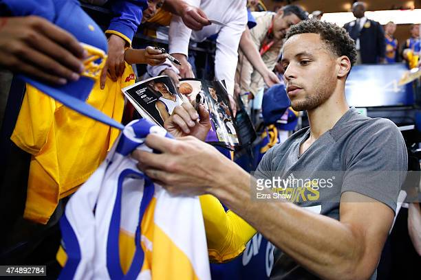 Stephen Curry of the Golden State Warriors signs autographs before taking on the Houston Rockets in game five of the Western Conference Finals of the...