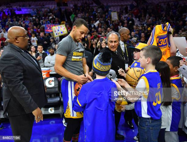 Stephen Curry of the Golden State Warriors signs autographs for young fans against the Philadelphia 76ers at Wells Fargo Center on February 27 2017...