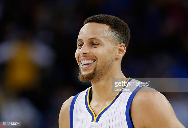 Stephen Curry of the Golden State Warriors smiles after making a threepoint basket against the Orlando Magic at ORACLE Arena on March 7 2016 in...