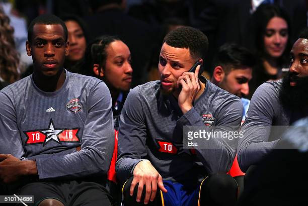 Stephen Curry of the Golden State Warriors speaks on a cell phone on the bench in the Taco Bell Skills Challenge during NBA AllStar Weekend 2016 at...