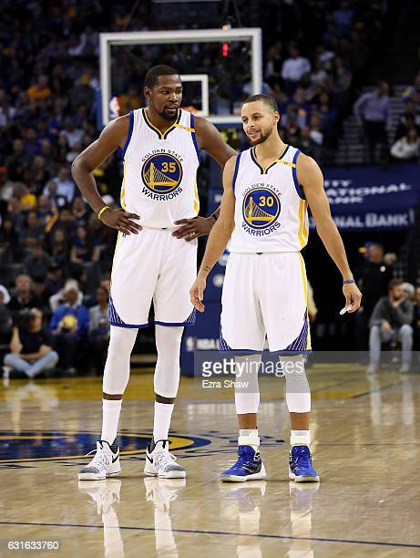 Stephen Curry of the Golden State Warriors stands next to Kevin Durant of the Golden State Warriors during their game against the Detroit Pistons at...