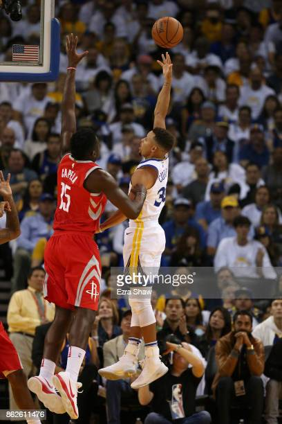 Stephen Curry of the Golden State Warriors takes a shot against Clint Capela of the Houston Rockets during their NBA game at ORACLE Arena on October...