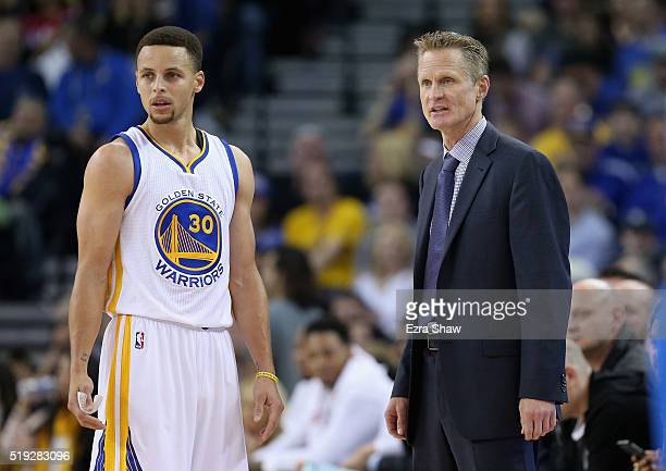Stephen Curry of the Golden State Warriors talks to head coach Steve Kerr during their game against the Dallas Mavericks at ORACLE Arena on March 25...