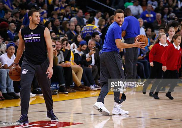 Stephen Curry of the Golden State Warriors talks to Seth Curry of the Sacramento Kings before their game at ORACLE Arena on December 28 2015 in...