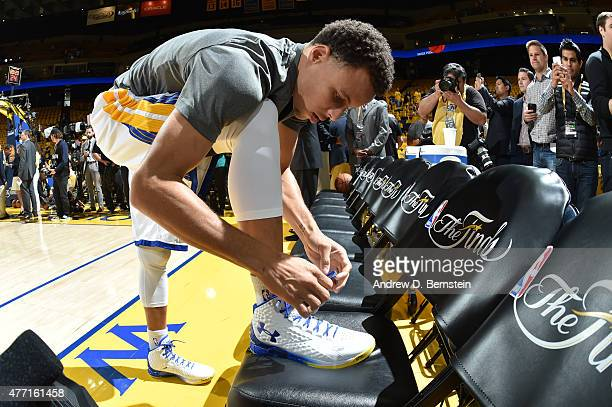 Stephen Curry of the Golden State Warriors ties his sneakers before Game Five of the 2015 NBA Finals at Oracle Arena on June 14 2015 in Oakland...