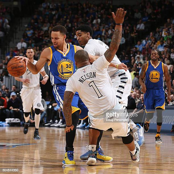Stephen Curry of the Golden State Warriors tries to retain control of the ball against the defense of Jameer Nelson and Gary Harris of the Denver...