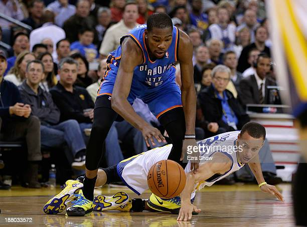 Stephen Curry of the Golden State Warriors tries to steal the ball from Kevin Durant of the Oklahoma City Thunder at ORACLE Arena on November 14 2013...