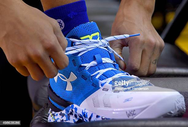 Stephen Curry of the Golden State Warriors tying his Under Armour basketball shoe prior to playing the Los Angeles Lakers in an NBA basketball game...
