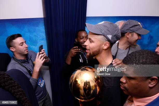 Stephen Curry of the Golden State Warriors walks through the hallways with the Larry O'Brien Trophy after winning Game Five of the 2017 NBA Finals...