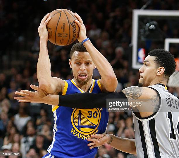 Stephen Curry of the Golden States Warriors is defended by Danny Green of the San Antonio Spurs at ATT Center on March 19 2016 in San Antonio Texas...