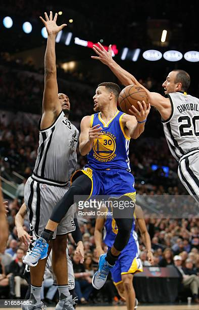Stephen Curry of the Golden States Warriors looks to pass after driving between Boris Diaw of the San Antonio Spurs and Manu Ginobili of the San...