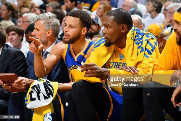 Stephen Curry talks with Kevin Durant of the Golden State Warriors during the game against the San Antonio Spurs during Game Three of the Western...